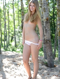 Adorable long haired teen chick taking off clothes in the shade of the trees near the sea.