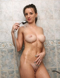 Tanned model Sissy poses nude in a bathroom taking a shower
