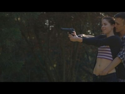 Amber Nevada is on an interesting date, where her boyfriend Kendo Ortiz is showing her how to shoot a gun. Despite Amber's distracting kisses and licks, Kendo is able to hit the first target. Determined now to get her guy's attention, Amber wraps her arms around Kendo's waist and slips her hands down his pants.Kendo gets off one more shot before Amber gets serious about taunting him. Dropping to her knees in front of her lover, Amber pulls out his stiffie and starts sucking him off like a Hoover. When Kendo tries to put the gun down, Amber makes it clear that she wants him to keep shooting so that she can enjoy the way she affects his concentration as she treats his dick like her own personal lollipop.Turning the tables on Amber, Kendo helps her to her feet and then hands her the gun. He comes up from behind her as he explains to her how to aim the weapon, and then slides his hand down her pants so that he can fondle her clit while she shoots. In only a few moments Amber decides that she's no longer interested in playing this game, so she drops the gun to the ground and spins around to give Kendo a true, loving kiss.Kendo is happy to shift his focus to pulling up Amber's shirt so that he can lavish attention on her pierced nipples and small boobs. Soon, Amber has pulled down her pants and gotten down on her hands and knees on the ground to offer herself for Kendo. He's happy to deliver a doggy style pussy pounding, sinking his cock balls-deep in Amber's bald twat.Laying down on his back, Kendo pulls Amber on top of him so that she can sink down onto his fuck stick and set the pace on her own. With her hands clutching her little boobs, Amber gladly takes control. She's so turned on that it's not long before her cowgirl style ride has brought her to a climax that leaves her whole body spasming in pleasure.  Kneeling beside Kendo, Amber gets to work with her hands rubbing and stroking his stiffie. Delighted by the friction, Kendo takes a short time to enjoy the sensation before exploding his seed all over Amber's hands and his own belly.